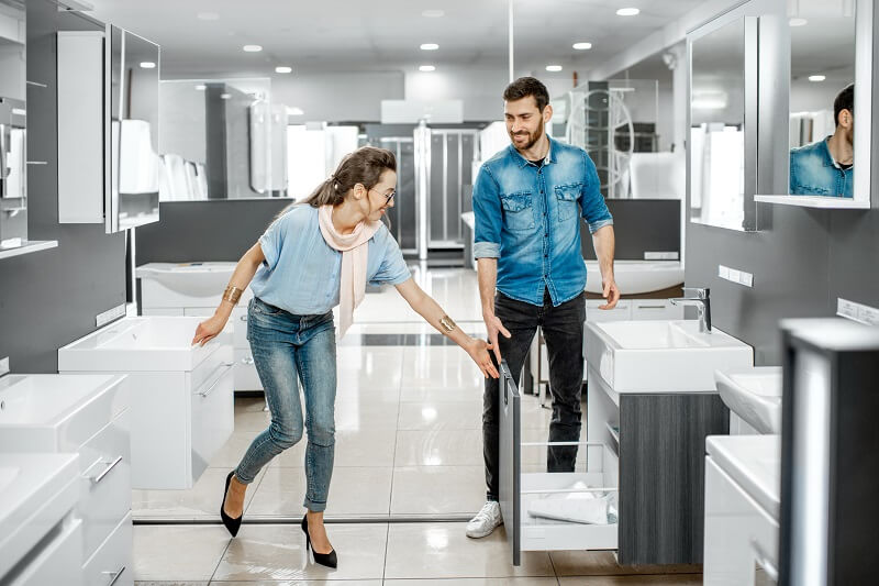A young couple visiting a bathroom renovation showroom and chosing a cabinet